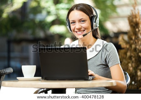 Young woman using laptop and chatting in cafe #400478128