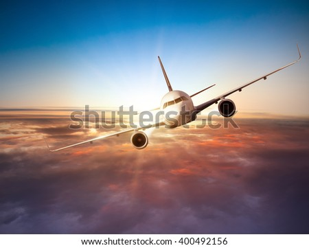 Airplane flying above clouds in dramatic sunset #400492156