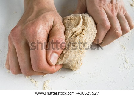 Kneading dough . Close up image of a young woman's hands kneading wholegrain dough. #400529629