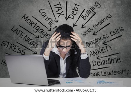 Picture of female Indian entrepreneur with a laptop and financial charts on the table, looks stressful thinks her problems