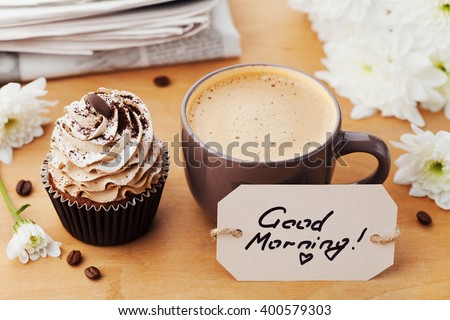 Coffee mug with cupcake, flowers, newspaper and notes good morning on rustic table, sweet dessert for breakfast, lifestyle