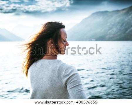 Beautiful girl with tousled hair on the background of the Bay in Montenegro #400596655