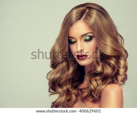 Beautiful girl with long wavy hair .  fair-haired  model  with curly hairstyle   and fashionable makeup . Bright purple lips #400629601