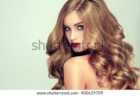 Beautiful girl with long wavy hair .  fair-haired  model  with curly hairstyle   and fashionable makeup . Bright purple lips #400629709