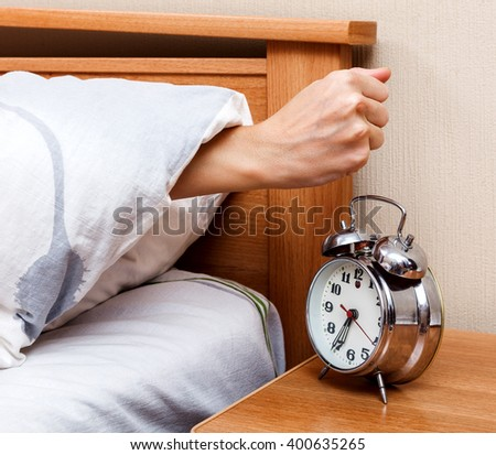 Woman stopping the alarm clock in the bedroom #400635265