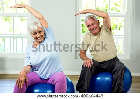 Portrait of smiling senior man and woman exercising at health club #400664449