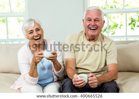 Portrait of happy senior couple holding coffee cups while sitting on sofa at home #400665526