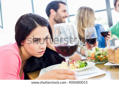 Drunk woman looking at wine glass while having meal with friends #400680055