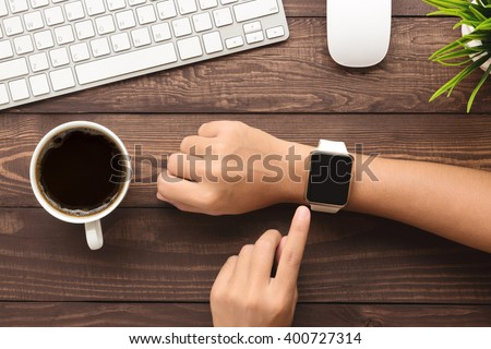 hand using smartwatch on desk top view Royalty-Free Stock Photo #400727314