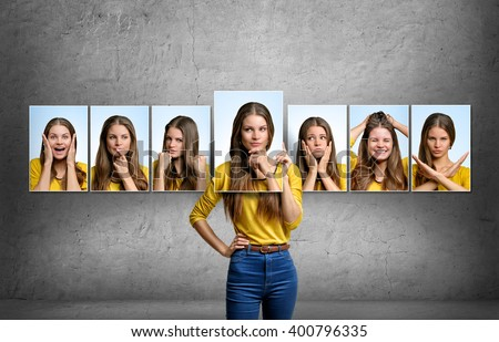Girl holds and changes her face portraits with different emotions Royalty-Free Stock Photo #400796335