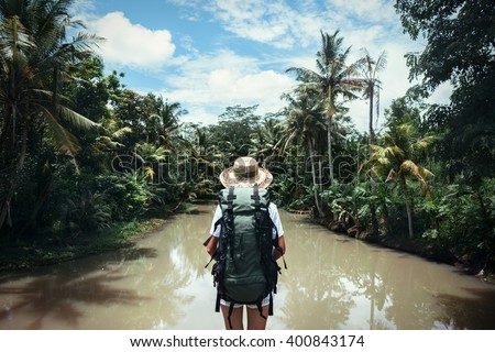 Traveling woman with backpack and straw hat looking at tropical river at sunny day Royalty-Free Stock Photo #400843174
