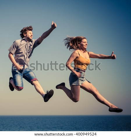 Carefree young couple friends jumping by sea ocean water. Happy woman and man having fun. Summer happiness and freedom. #400949524