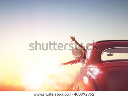 Toward adventure! Girl relaxing and enjoying road trip. Happy girl rides into the sunset in vintage car. Royalty-Free Stock Photo #400992952