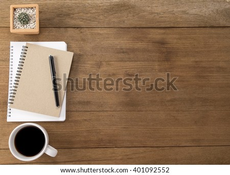 Office desk table with smartphone, pen on notebook, cup of coffee and flower. Top view with copy space (selective focus) #401092552
