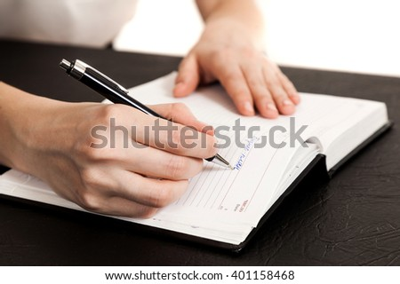 female hands a close up writing in the daily log #401158468