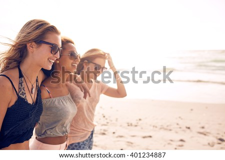 Group of happy young women walking on a beach. Three female friends strolling along the sea shore on a summer day, enjoying vacation. #401234887