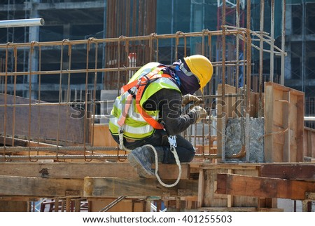 MALACCA, MALAYSIA -OCTOBER 13, 2015: Construction workers fabricating steel reinforcement bar at the construction site in Malacca, Malaysia #401255503