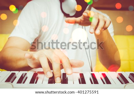 musician hands playing piano with colourful bokeh Royalty-Free Stock Photo #401275591