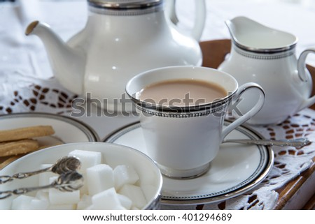 English cup of tea with teapot, sugar and biscuits #401294689