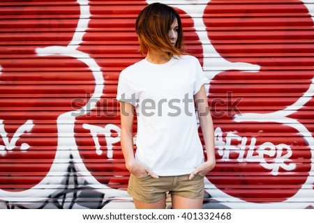 young attractive girl wearing a white t-shirt standing on a graffiti wall background  #401332468
