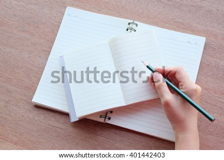 hand is writing on blank notebook on wood textures  #401442403