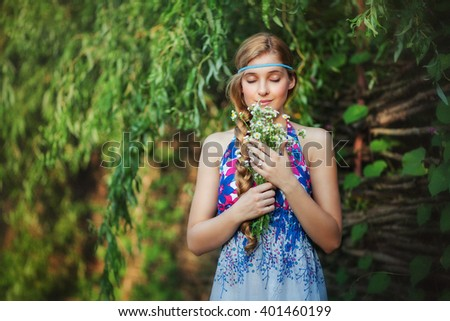 Beauty young model standing outdoors and holding a bouquet of white flowers. Pretty female smelling flowers with closed eyes. Beautiful girl with long blonde braid  enjoying outdoors.   #401460199