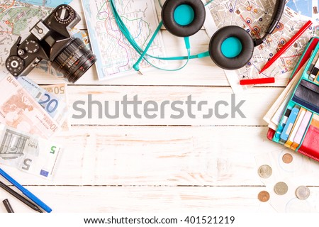 Camera, touristic maps, headphones, wallet with credit cards, phone, colorful pens, euro banknotes and coins on the white desk. Travel background. Journey planning. Tourist essentials. Space for text #401521219