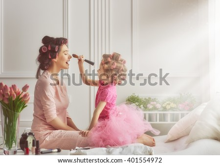 Happy loving family. Mother and daughter are doing hair and having fun. Mother and daughter doing your makeup sitting on the bed in the bedroom. Royalty-Free Stock Photo #401554972