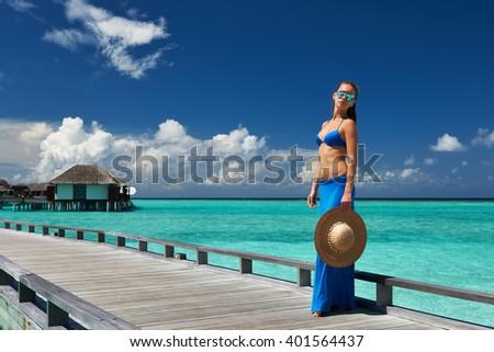 Woman on a tropical beach jetty at Maldives #401564437