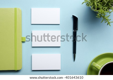Business card blank, notepad, flower, coffee cup and pen at office desk table top view. Corporate stationery branding mock-up