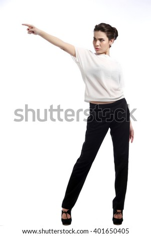 close-up portrait of young brunette in business style,  in white blouse and black trousers on the  light background studio #401650405