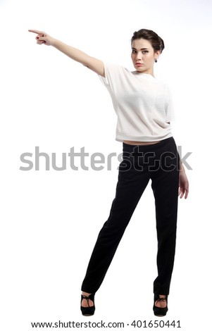 close-up portrait of young brunette in business style,  in white blouse and black trousers on the  light background studio #401650441