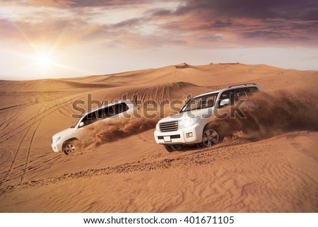 two 4x4 vehicles bashing side to side through the desert dunes in the evening sun