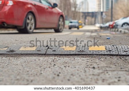 Car passing through the speed bump on the road                            #401690437
