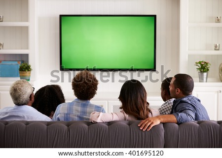 Multi generation family watching TV at home, back view Royalty-Free Stock Photo #401695120