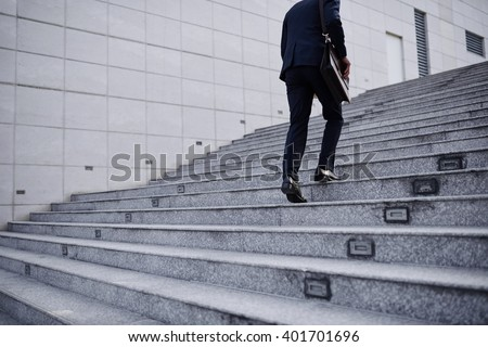 Cropped image of business person going up the stairs Royalty-Free Stock Photo #401701696