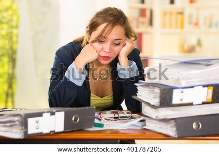 Business woman sitting by desk, paper files spread out, leaning head on hands looking overwhelmed and tired #401787205