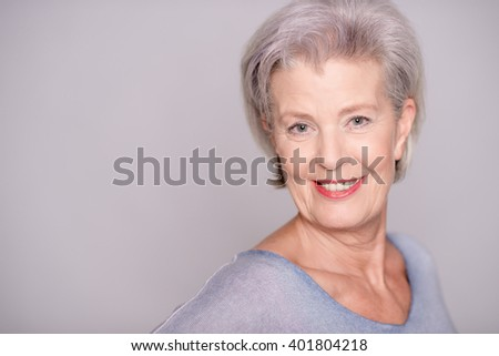 Portrait of a smiling senior woman in front of gray background #401804218