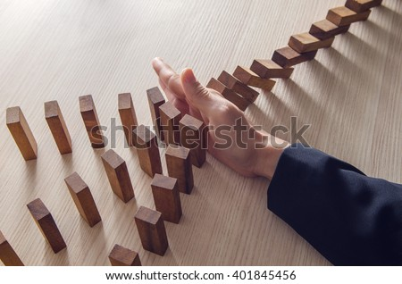 Businesswoman hand stopping the domino wooden effect concept for business. Royalty-Free Stock Photo #401845456