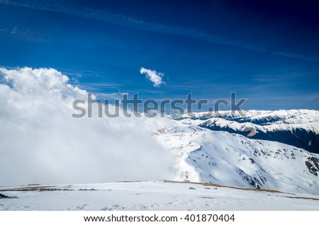 Winter landscape in the mountains. Mountain ridges covered by snow in  winter in Europe. #401870404