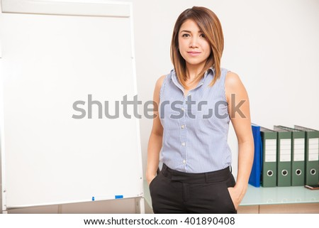 Portrait of a beautiful young Latin teacher standing in a classroom next to a flip chart #401890408