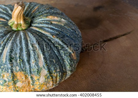 Pumpkin is a fresh vegetable have a green and yellow color on a wooden table #402008455