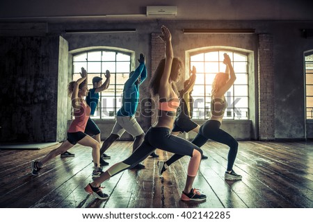Group of sportive people in a gym training - Multiracial group of athletes stretching before starting a workout session Royalty-Free Stock Photo #402142285