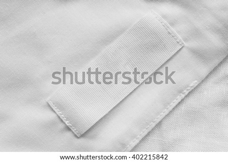 White blank clothes label on white linen as a background #402215842