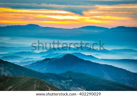 Sunset in the mountains. Dramatic colorful clouds over blue hills #402290029