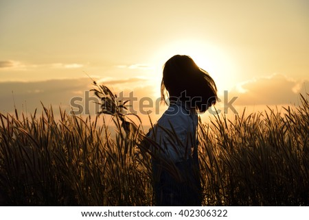 A silhouette of a happy girl outside picking wild flowers in the meadow at sunset.