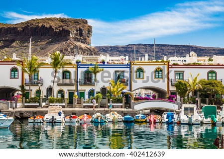Traditional Colorful Buildings With Boats In Front And Mountain In The Background - Puerto de Mogan, Gran Canaria, Canary Islands, Spain #402412639