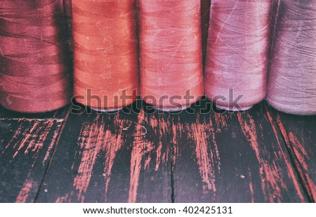 Retro photo thread spools in red scale sewing and needlework on the background of the old wooden table #402425131
