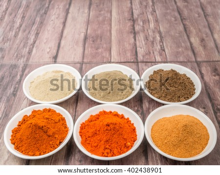 Various type of chili powder in white bowl over wooden background #402438901