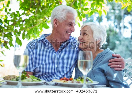 Cheerful retired couple with arm around while sitting at table #402453871